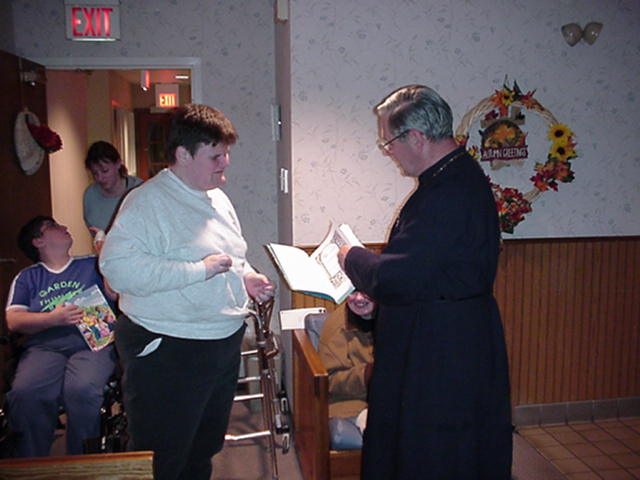 Father Andrew presenting a bible to a resident.