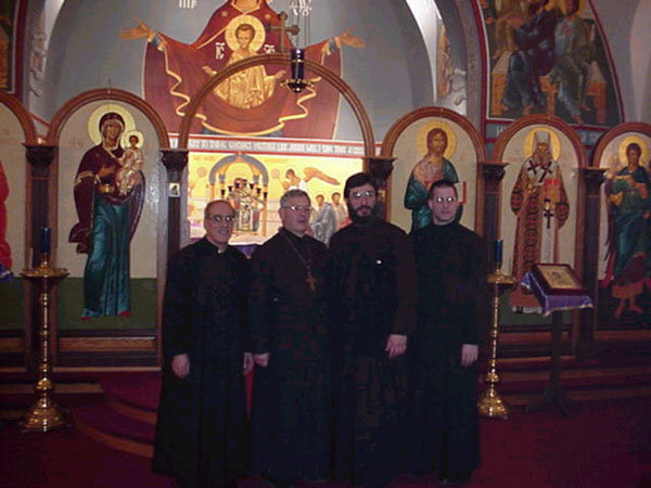 Clergy pose for a picture in front of iconastasis.