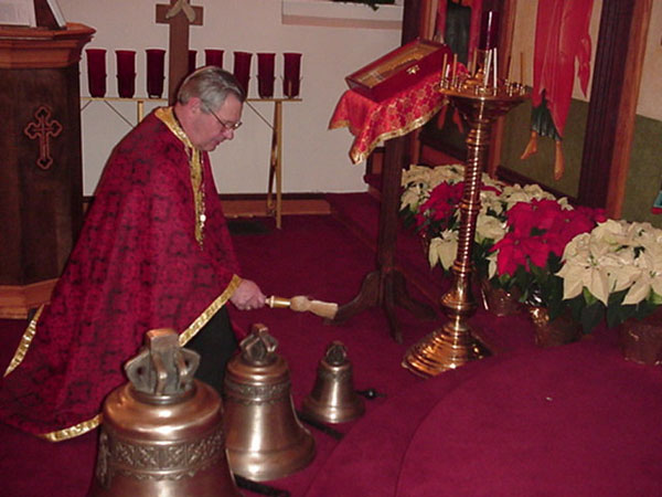 Priests blesses bells with Holy Water