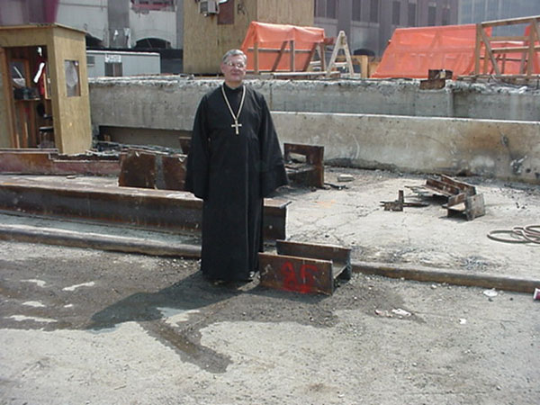 Father Andrew standing at the Site of the former World Trade Center with the beam which he brought back to St. Luke in Palos Hills