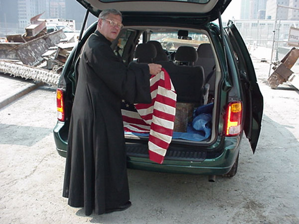 Father Andrew Places Flag Over Memorial