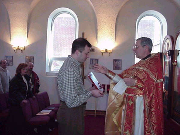 Dan receives his icon from Father Harrison.