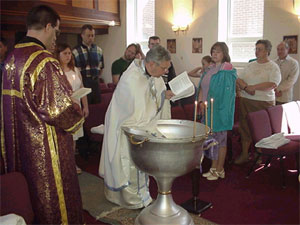 Father Andrew prepares the Baptismal Font.