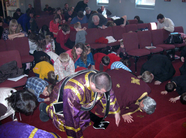 Parishioners bow down before the Cross