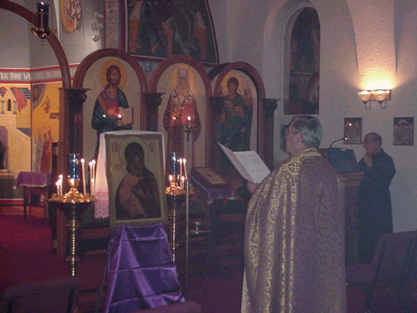 Father Harrison reads prayers in front of the Icon of the Virgin.