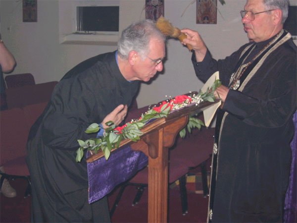 Father Andrew blesses congregation with rose water.