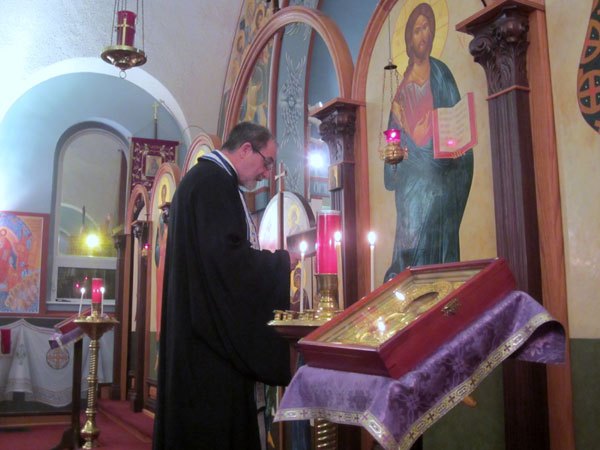 Father Paul reads prayers in front of the Icon of the Virgin.